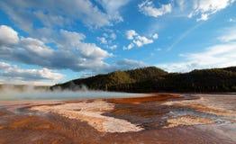 A mola quente prismático grande sob o por do sol nubla-se na bacia intermediária do geyser no parque nacional de Yellowstone em W Foto de Stock