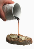 Molasses. Pouring molasses on buttered bread stock photography