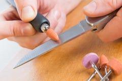 Molatura del coltello vecchio con la mola rotatoria fotografia stock libera da diritti