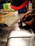 Molatura manuale dell'uomo asiatico del tecnico del primo piano in superficie della muffa Fotografia Stock