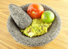 Molcajete Mortar Bowl and Pestle Filled With Guacamole And Ingre. Molcajete mortar bowl and pestle filled with guacamole, tomato,and lime on a wooden table Stock Photography