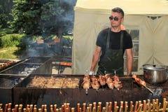 Moldau, Kishinev 23, 05 2015 La friture de jeune homme de Fest de BBQ un chiche-kebab et un poulet grillent tout entier dehors Image stock
