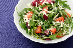 Moldavian salad with arugula cherry tomatoes and cheese. Arugula, moldavian cheese and cherry tomatoes with olive oil close-up Royalty Free Stock Photo