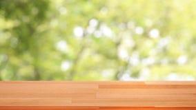 Molde de madeira vazio da tabela na parte superior com o fundo do verde da natureza que move-se com o ventoso atrav?s das ?rvores filme