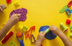 Molde del niño del plasticine coloreado Mano del ` s de los niños foto de archivo libre de regalías