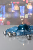 Molde do cartão feito da vela azul com fita azul, as bolas de prata do Natal, corda de grânulos de prata e lig colorido do bokeh Foto de Stock Royalty Free