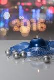 Molde do cartão feito da vela azul com fita azul, as bolas de prata do Natal, corda de grânulos de prata e lig colorido do bokeh Imagens de Stock