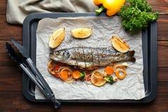 Molde para el horno con los pescados de la lubina Imagenes de archivo