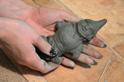 Molded from clay. Clay toy in his hands. Modelling royalty free stock image