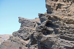 POROUS ROCK IN LAYERS. Molded grey rock layers at the coast Stock Photography