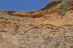 MOLDED ROCK FORMATION. Molded rock layers on a sandy bluff at the coast Royalty Free Stock Photo