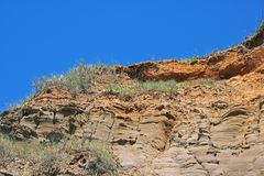 SANDY BLUFF WITH MOULDED ROCK FORMATION. Molded rock layers on a sandy bluff at the coast Royalty Free Stock Images