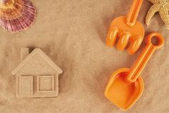 Molded sand house and plastic toys, laying on the beach. Stock Photo