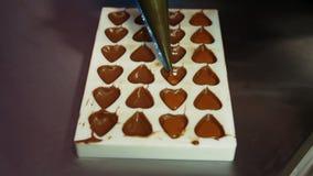 Moldes de relleno del chocolate del trabajador con el chocolate derretido almacen de metraje de vídeo