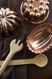 Moldes del cobre con artículos de cocina de madera Imagenes de archivo