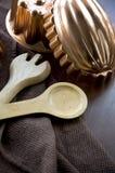 Moldes del cobre con la cuchara de madera Fotos de archivo