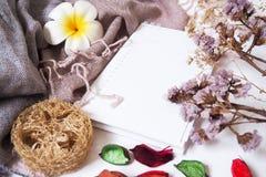 Moldes do fundo com espaço vazio do texto em cadernos na tela e nas flores secadas decorativas foto de stock