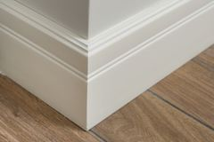 Molding in the interior, baseboard corner. Light matte wall with tiles immitating hardwood flooring.  Stock Photography
