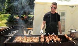 Moldova, Chisinau - 23 05 2015 BBQ fest młodego człowieka dłoniak shish Zdjęcie Stock