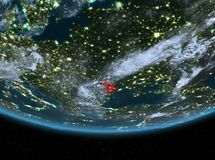 Moldova at night. Highlighted in red on planet Earth with clouds. 3D illustration. Elements of this image furnished by NASA Royalty Free Stock Photography