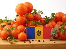 Moldovan Flagge auf einer Holzverkleidung mit den Tomaten lokalisiert auf einem Whit Lizenzfreies Stockbild
