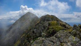 Moldoveanu ragen, Karpatenberge, Fagaras, Rumänien empor. Gebirgsrücken in den Wolken. Lizenzfreie Stockfotos