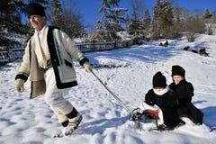 Moldovita, Roumanie, le 30 novembre 2018 : Grand-père tirant le traîneau avec des enfants de manière traditionnelle dans Bucovina photos stock