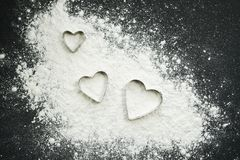 Molds in the form of a heart for cutting dough on white wheat flour on a black background. Molds form heart cutting dough white wheat flour black background stock photos