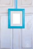 Moldura para retrato de turquesa que pendura na porta branca afligida Fotos de Stock Royalty Free