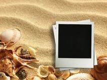 Moldura para retrato em shell e em fundo da areia imagem de stock royalty free