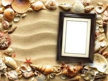 Moldura para retrato em shell e em fundo da areia imagens de stock royalty free
