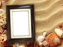 Moldura para retrato em shell e em fundo da areia imagens de stock