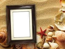 Moldura para retrato em shell e em fundo da areia imagem de stock