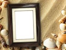 Moldura para retrato em shell e em fundo da areia fotografia de stock royalty free