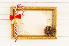 Moldura para retrato vazia com os doces do bastão do Natal na madeira Foto de Stock
