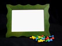Moldura para retrato verde com os penhores no fundo preto Imagem de Stock