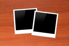 Molduras para retrato vazias na tabela de madeira Imagens de Stock