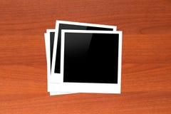 Molduras para retrato vazias na tabela de madeira Foto de Stock Royalty Free
