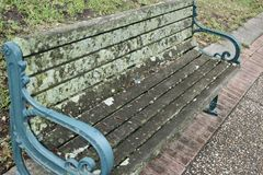 Moldy Bench With Mold. A very moldy bench left over from the winter weather as it approaches spring with blue painted metal armrests stock photography