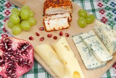 Moldy cheese pepper cheese and emmental grapes assorted with pomegranate and grapes on wood cheese tasting delicacy concept. Photo Royalty Free Stock Image
