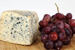 Moldy cheese and red grapes Royalty Free Stock Images