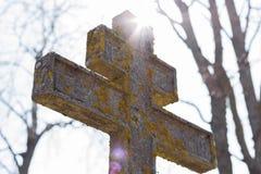 Moldy cross and shining sun. Moldy stone cross and shining sun Royalty Free Stock Photo