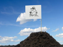 Mole mound. With white flag showing mole icon affixed over blue sky stock photo