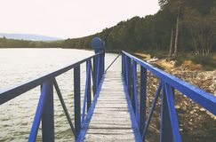 Mole pier on the scandinavian lake with motorboat on side and misty hills. Blue wooden bridge in forest in autumn time with blue Royalty Free Stock Photography