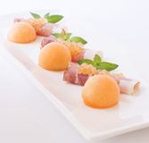 Molecular melon caviar, prosciutto and fresh melon Stock Photography