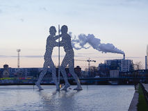 Molecule man on river Spree, Berlin, with smoking chimney in the back Royalty Free Stock Image