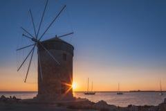 Molen op de achtergrond van de het toenemen zon in de haven van Mandraki Het eiland van Rhodos Griekenland Royalty-vrije Stock Foto