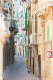 Molfetta, Apulia - A black cat tiptoeing through a historic alleyway in Molfetta royalty free stock photo