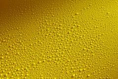 Molhe as gotas que perlam em uma superfície de metal amarelo Imagem de Stock Royalty Free