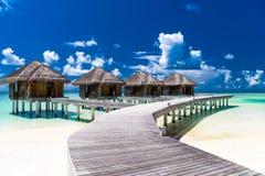 Molhe bungalows com o céu azul e o mar bonitos em Maldivas Fotografia de Stock